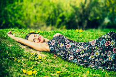 Pretty brunette woman relaxing on te grass in the park Royalty Free Stock Photography