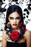 Pretty brunette woman with rose jewelry, black and red, bright m Royalty Free Stock Images