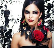 Pretty brunette woman with rose jewelry, black and red, bright m Stock Photos