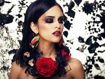 Pretty brunette woman with rose jewelry, black and red, bright m Stock Image