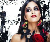 Pretty brunette woman with rose jewelry, black and red, bright m Stock Images