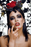 Pretty brunette woman with rose jewelry, black and red, bright make up kike a vampire Royalty Free Stock Images