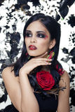 Pretty brunette woman with rose jewelry, black and red, bright make up kike a vampire closeup red lips Royalty Free Stock Image