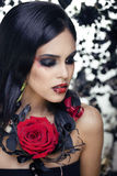 Pretty brunette woman with rose jewelry, black and red, bright make up kike a vampire closeup red lips Stock Images