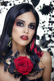 Pretty brunette woman with rose jewelry, black and red, bright make up a vampire closeup red lips Royalty Free Stock Photos