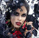 Pretty brunette woman with rose jewelry, black and red, bright make up kike a vampire closeup red lips Stock Photos