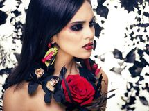 Pretty brunette woman with rose jewelry, black and red, bright m Royalty Free Stock Image
