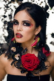 Pretty brunette woman with rose jewelry, black and red Stock Photography