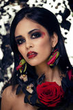 Pretty brunette woman with rose jewelry, black and red Royalty Free Stock Image