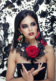 Pretty brunette woman with rose jewelry, black and red Stock Photos