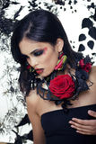 Pretty brunette woman with rose jewelry, black and red Stock Photo
