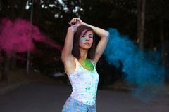 Pretty  tanned woman with short hair posing with exploding Holi Stock Images