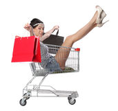 Pretty brunette woman sits in an empty shopping trolley with a s Royalty Free Stock Photo