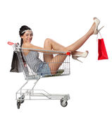 Pretty brunette woman sits in an empty shopping trolley with a s Stock Images