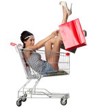 Pretty brunette woman sits in an empty shopping trolley with a s Stock Image