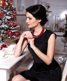 Pretty brunette woman sitting beside a decorated Christmas tree Royalty Free Stock Photo