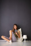 Pretty brunette woman sitting on the floor with a pillow and plane table Royalty Free Stock Photos
