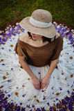 Pretty brunette woman sitting with a flowered skirt. View from a Royalty Free Stock Photo