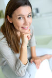 Pretty brunette woman sitting at home with hand under chin royalty free stock images