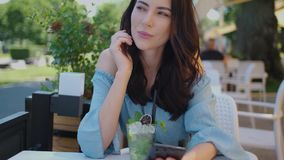 Pretty brunette woman sitting in outdoor restaurant and using her mobile phone. Summer time in the city stock footage