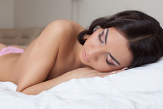 Pretty brunette woman sleeping in bedroom Stock Photos