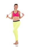 Pretty brunette woman in sports neon yellow leggings and pink bra posing with long skipping-rope. Stock Photos