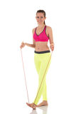 Pretty brunette woman standing and stretching a long skipping-rope. Stock Image