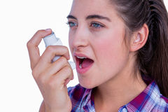 Pretty brunette woman using asthma inhaler Royalty Free Stock Image