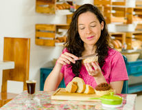 Pretty brunette woman wearing pink shirt sitting by table inside bakery, applying butter to slice of bread smiling Stock Photography