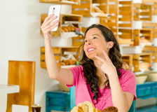 Pretty brunette woman wearing pink shirt sitting by table inside bakery, holding up mobile phone taking a selfie Stock Images