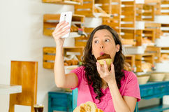 Pretty brunette woman wearing pink shirt sitting by table inside bakery, holding up mobile phone taking a selfie Royalty Free Stock Photography