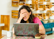 Pretty brunette woman wearing pink shirt sitting by table inside bakery, looking at laptop screen covering her eyes with Royalty Free Stock Photos