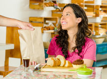 Pretty brunette woman wearing pink shirt sitting by table inside bakery, receiving brown paper bag from waiter and Stock Photo