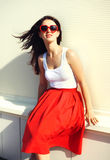 Pretty brunette woman wearing a red sunglasses and skirt Royalty Free Stock Images