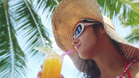 Pretty brunette woman wearing sunglasses and hat with tropical cocktail on the beach enjoying sunny weather in slow. Pretty woman wearing sunglasses and hat with stock video footage
