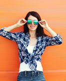 Pretty brunette woman wearing a sunglasses over colorful Royalty Free Stock Image