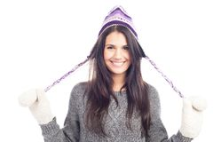 Pretty brunette woman with a woolen Peruvian hat a sweater and gloves smiling. And cheerful royalty free stock images