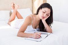 Pretty brunette writing and thinking on bed Stock Photo