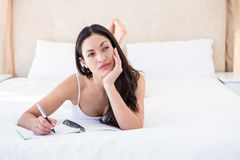 Pretty brunette writing and thinking on bed Royalty Free Stock Images