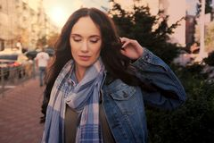 Pretty young female in jeans coat poses in a city street Royalty Free Stock Photos