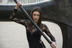 Pretty brunette young woman holding metal bar Stock Photography