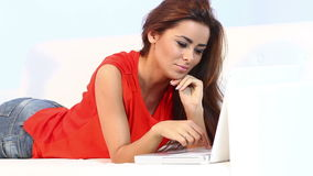 Pretty brunnette lying on sofa and working on computer stock footage