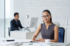 Business lady planning day. Pretty business lady in glasses taking notes in her notepad Stock Photo