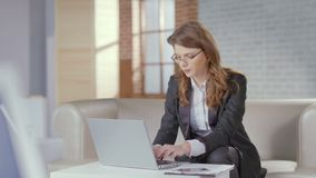 Pretty business lady in glasses typing on laptop, office worker. Stock footage stock video footage