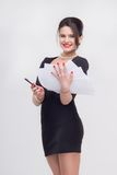 Pretty business lady standing with book. Enticing attractive young brunette woman standing with documents in half length in black dress, isolated on white Royalty Free Stock Images