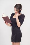Pretty business lady standing with book. Enticing attractive young brunette woman standing with book in full length in black dress,  on white background Stock Photography