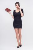 Pretty business lady standing with book. Tempting attractive young brunette woman standing with book in half length in black dress, isolated on white background Stock Photography