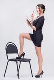 Pretty business lady standing with book. Tempting attractive young brunette woman standing with book in half length in black dress and one leg  on chair Royalty Free Stock Image