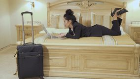 Pretty business lady uses laptop in a hotel room. Young businesswoman wearing black suit and with red lips lays on the bed in a hotel room. Pretty lady relaxes stock video