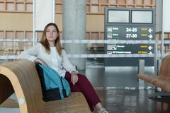 Pretty business woman with backpack sits while waiting for her flight Stock Images